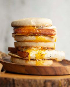 two sandwiches stacked on each other with yolk dripping down