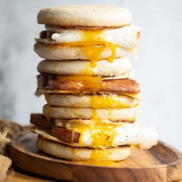 3 sandwiches stacked on each other on wooden board with yolk dripping out