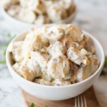 potato salad served in small white bowl on wooden board with second bowl blurred in background