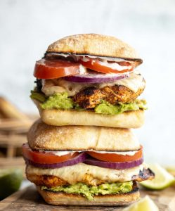 two cajun chicken sandwiches stacked on each other on wooden board surrounded by garnish