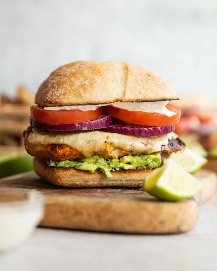 chicken avocado sandwich on wooden board with lime and mayo blurred in fornt