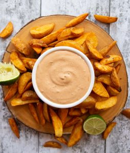 overhead shot of chipotle mayo in white pot surrounded by potato wedges