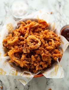 fried onions in wooden bowl with salt and bbq sauce blurred in background