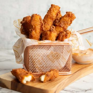 halloumi fries in small basket on wooden board with dip