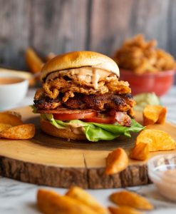 chicken sandwich on wooden board surrounded by potato wedges and dip