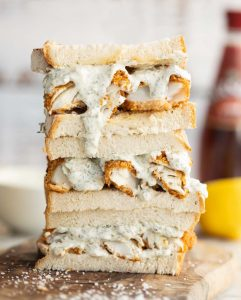 3 sandwich halves stacked on top of each other showing fish fingers and sauce