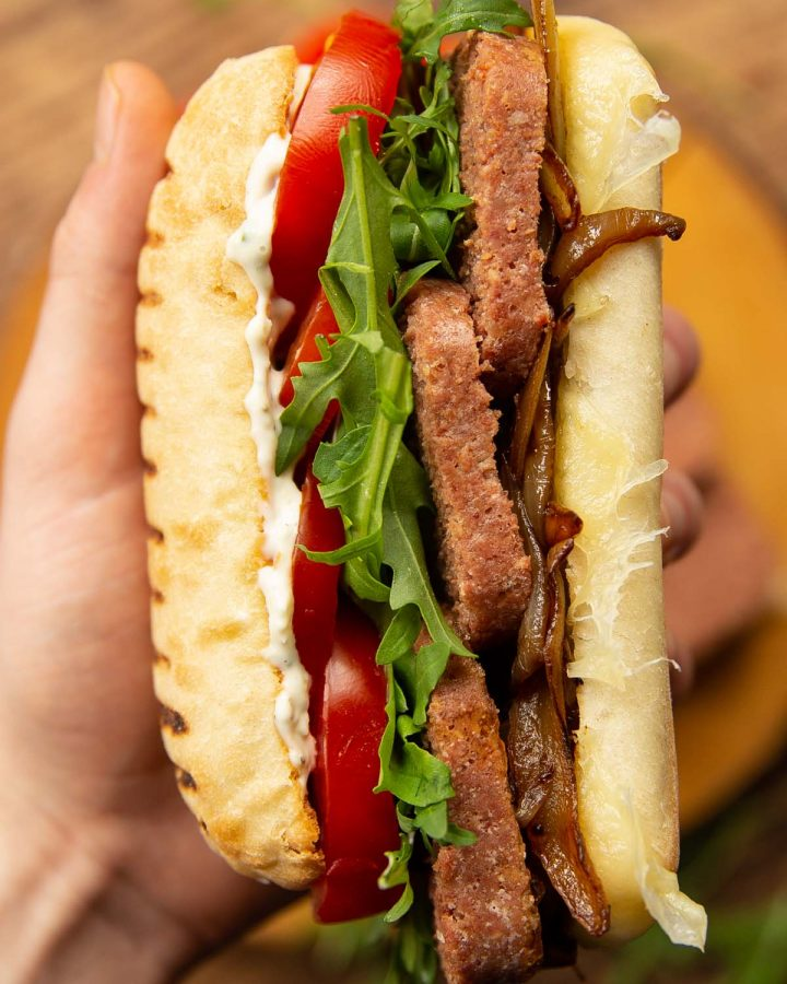 hand holding sandwich up close to camera above wooden board