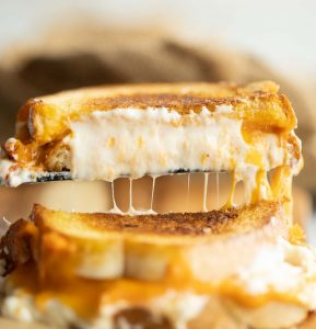 close up shot of spatula lifting half of sandwich with cheese dripping out