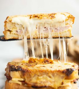 black spatula lifting half croque monsieur with cheese dripping out