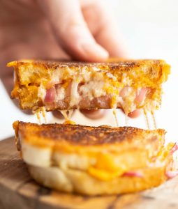 hand pulling sandwich half up with cheese pull