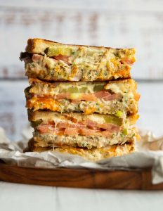 4 tuna melt halves stacked on each other on small wooden board