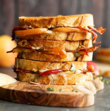 3 sandwiches stacked on each other on wooden board with apple and bread blurred in background