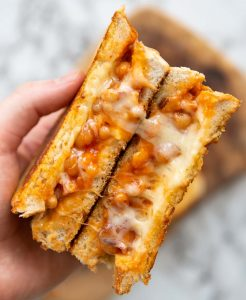 overhead shot of open sandwich showing cheesy beans above marble background