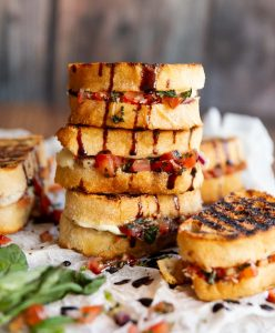 3 bruschetta sandwiches stacked on each other with balsamic glaze dripping down on to parchment paper and wooden board