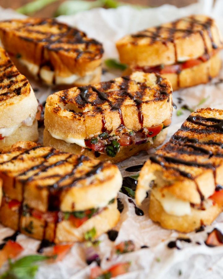 6 bruschetta sandwiches on crumpled parchment paper on wooden board with balsamic glaze
