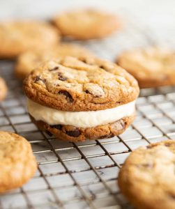 close up shot of cookie ice cream sandwich on wire rack with cookies