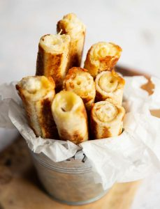 8 grilled cheese roll ups in a small tin on wooden board