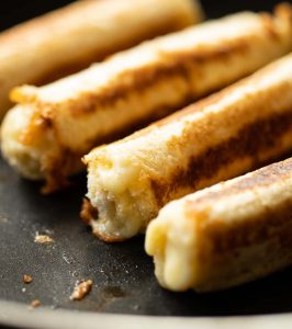 close up shot of grilled cheese roll ups in frying pan with cheese dripping out