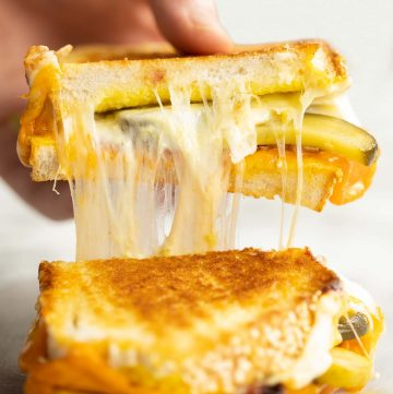 hand lifting up half of sandwich with pickles and cheese falling out