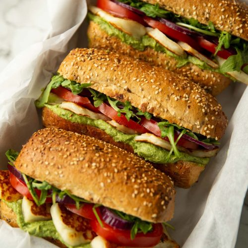 3 halloumi sandwiches in large white dish on marble background