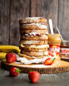 4 sandwiches stacked on each other on wooden board garnished with icing sugar and strawberries