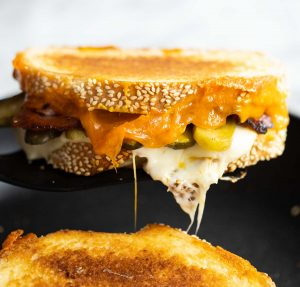 spatula lifting sandwich from pan with cheese dripping out