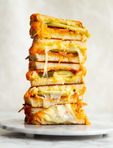 5 sandwich halves stacked on small marble board with cheese dripping out