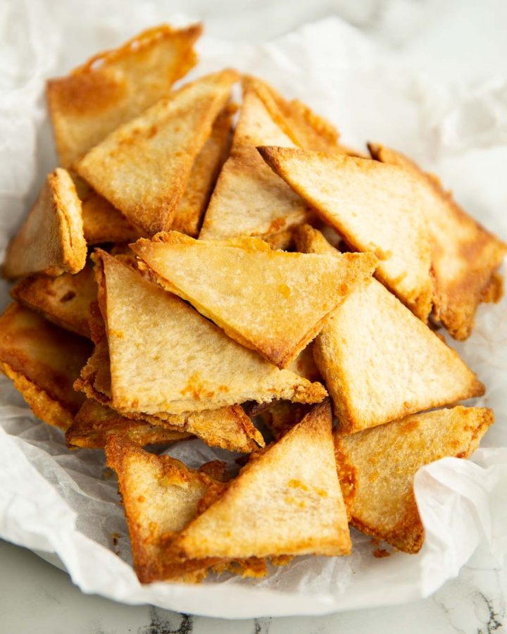 grilled cheese chips in crumpled parchment paper on marble backdrop