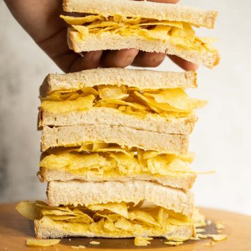 4 crisp sandwich halves stacked on each other with hand grabbing the top one