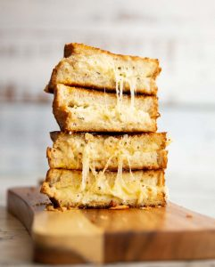 4 sandwich halves stacked on top of each other with cheese dripping out on wooden board