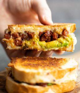 close up shot of hand lifting chorizo sandwich showing filling