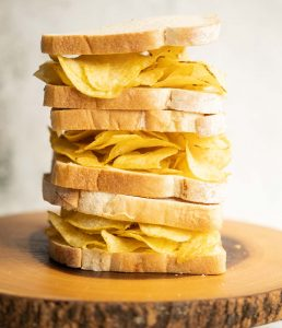 3 crisp sandwiches stacked on each other on wooden board