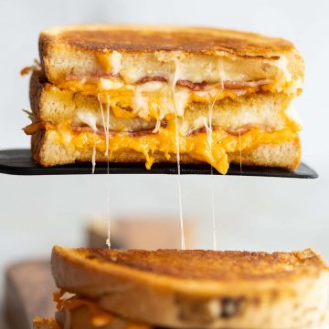 half of grilled cheese resting on black spatula with cheese dripping out
