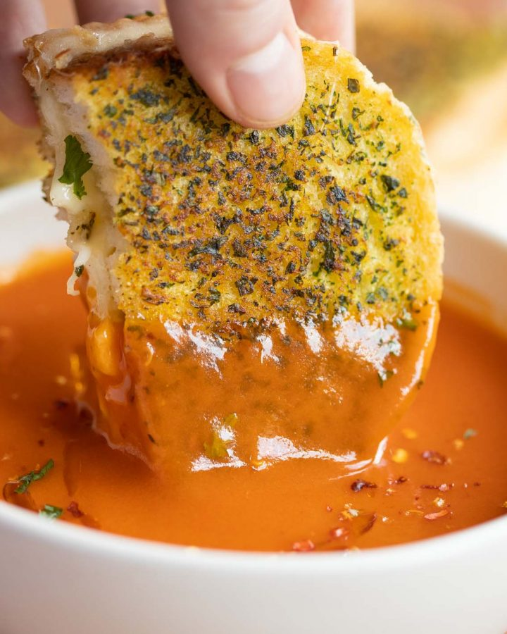 hand dunking grilled cheese into bowl of tomato soup