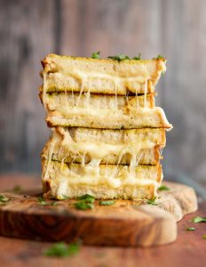 4 sandwiches halves stacked on each other on wooden board garnish with fresh parsley