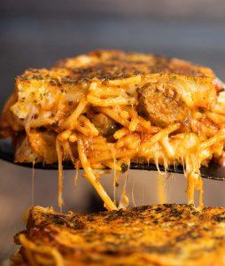 close up shot of black spatula lifting spaghetti sandwich showing filling