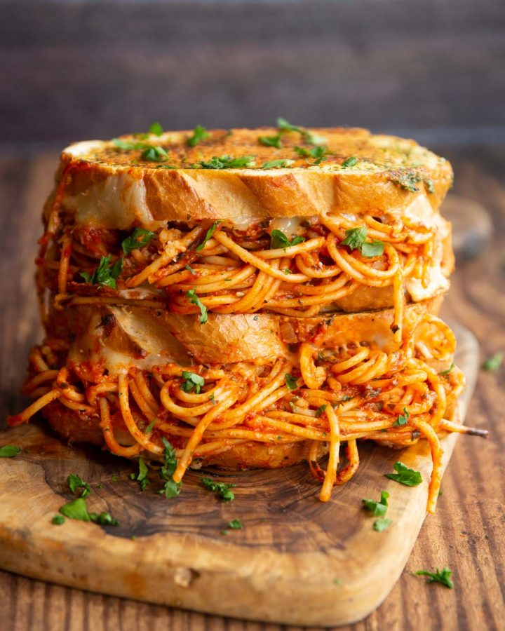 two spaghetti sandwiches stacked on each other on chopping board garnished with parsley