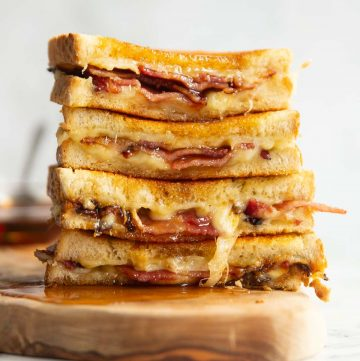 4 bacon grilled cheese halves stacked on each other on wooden board with maple syrup poured over