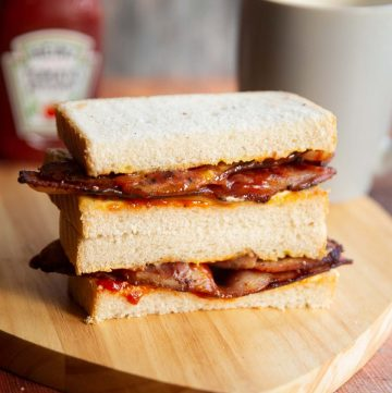 2 bacon sandwich halves stacked on each other with ketchup and cup of tea blurred in background