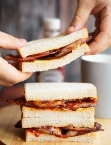 hands holding bacon sandwich above two others with ketchup and cup of tea blurred in background