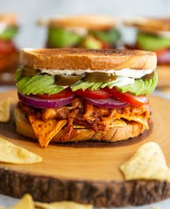chicken nacho sandwich on wooden board with more blurred in the background