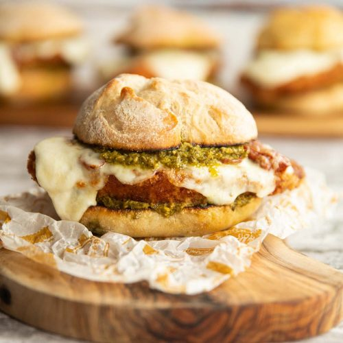 chicken pesto sandwich on wooden board with 3 more sandwiches blurred in background