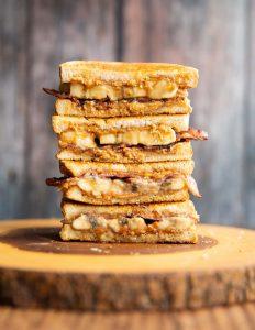 4 Elvis sandwich halves stacked on each other on wooden board