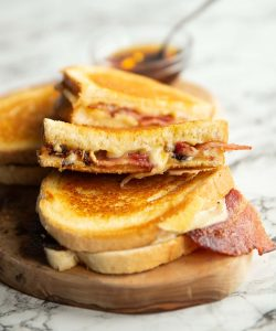 4 bacon grilled cheese halves on wooden board with small glass pot of maple syrup