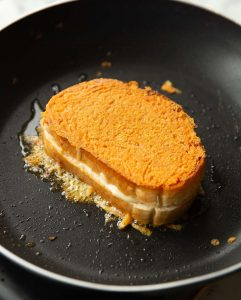 inside out grilled cheese in black pan with cheese oozing out