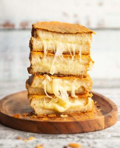 4 grilled cheese halves stacked on each other on small wooden board