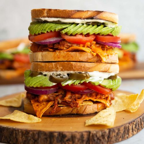 two nacho chicken sandwiches stacked on top of each other on wooden board with more blurred in background