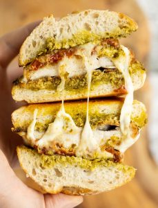 close up overhead shot of open chicken pesto sandwich showing filling