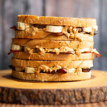 3 Elvis sandwiches stacked on each other on wooden board